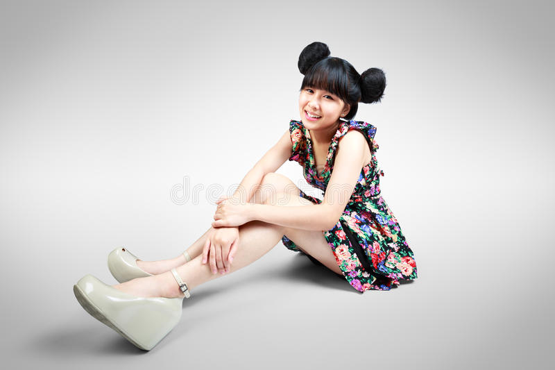Smiling teenage asian girl sitting on the floor stock image