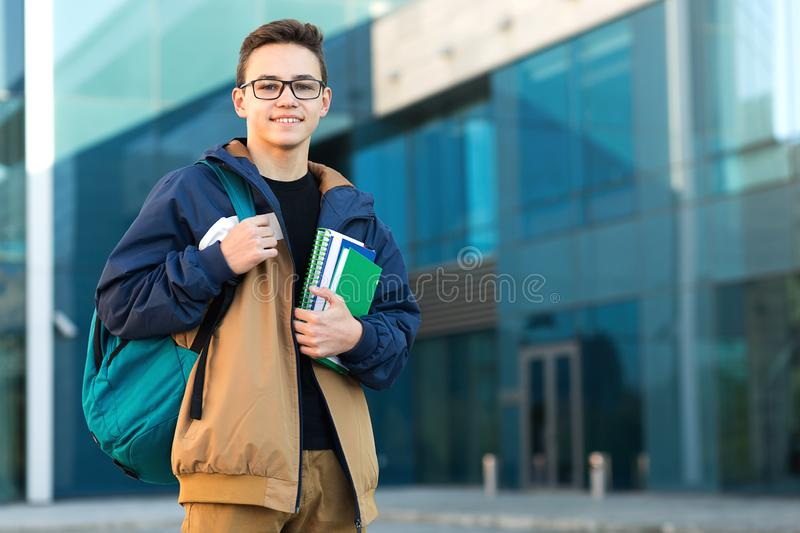 Smiling teenage boy with backpack and books. Standing near the urban building. Copy space royalty free stock images
