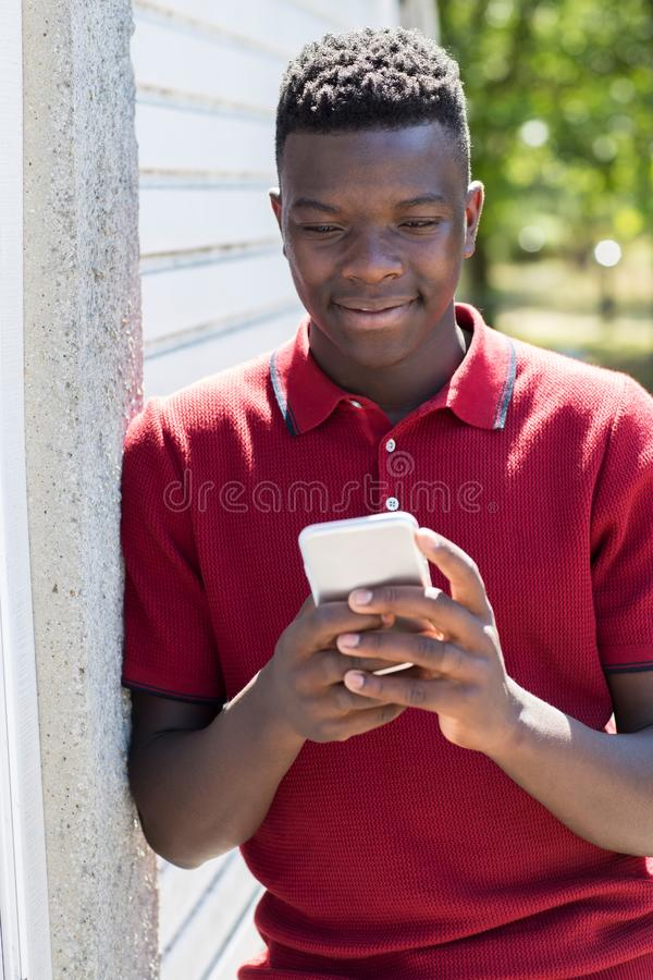 Teenage Boy Outdoors Sending Text Message From Mobile Phone. Smiling Teenage Boy Outdoors Sending Text Message From Mobile Phone royalty free stock photo