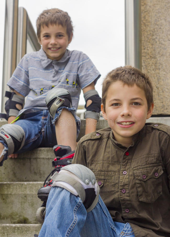 Smiling teenage boys in roller-blading protection kits. Two smiling teenage boys in roller-blading protection kits royalty free stock images