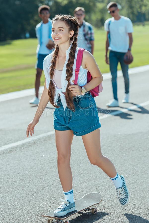 smiling teenage girl with backpack riding skateboard while classmates walking behind royalty free stock photo