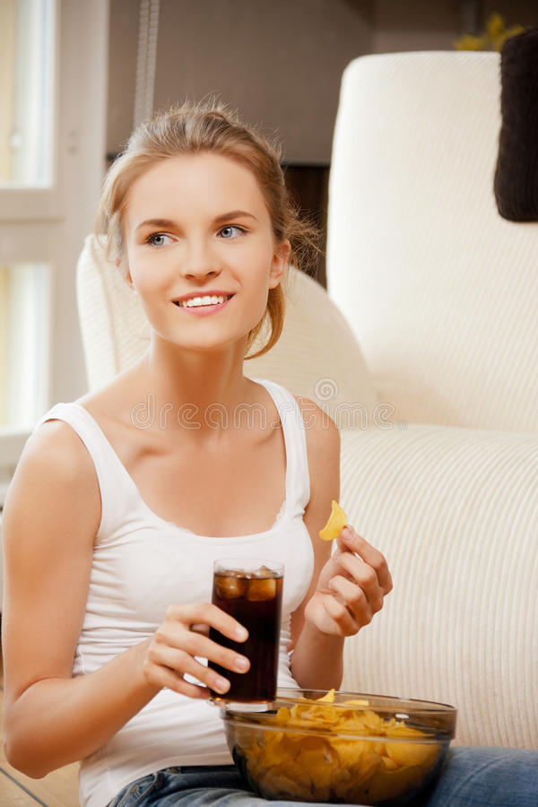 Download Smiling Teenage Girl With Chips And Coke Stock Photo - Image of happy, indoors: 39515124