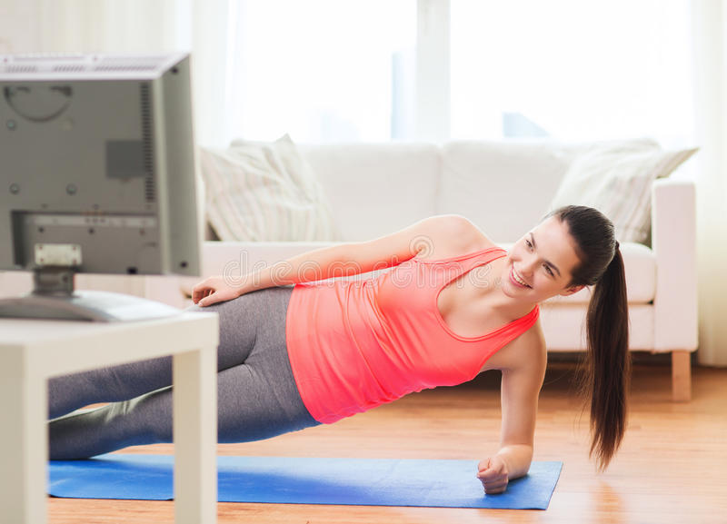 Smiling teenage girl doing side plank at home stock photography
