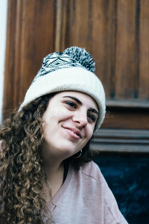 Smiling teenage girl with long and curly hair wearing a knit hat royalty free stock photo