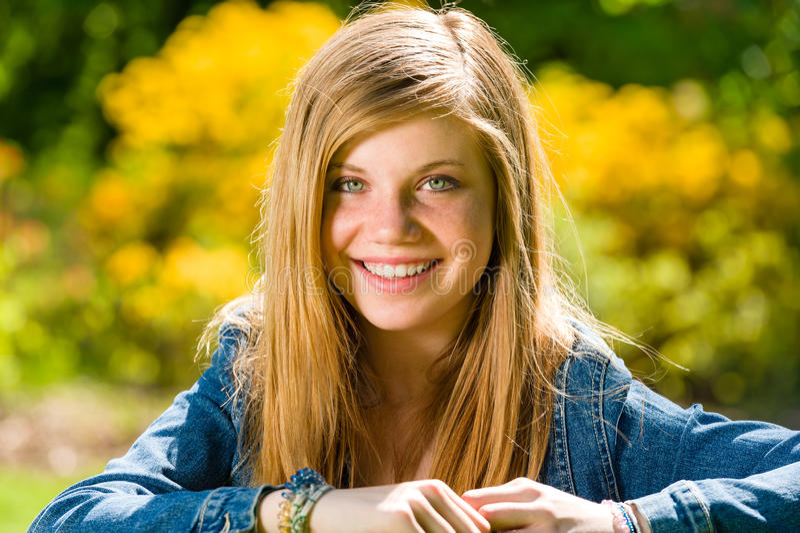 Smiling teenage girl looking at camera outdoors royalty free stock photo