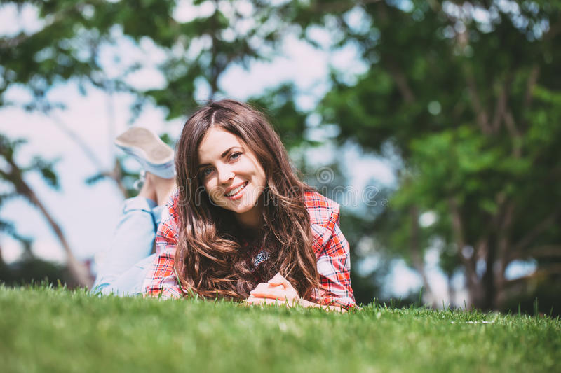 Smiling teenage girl lying on the grass in the park looking at the camera. stock photography