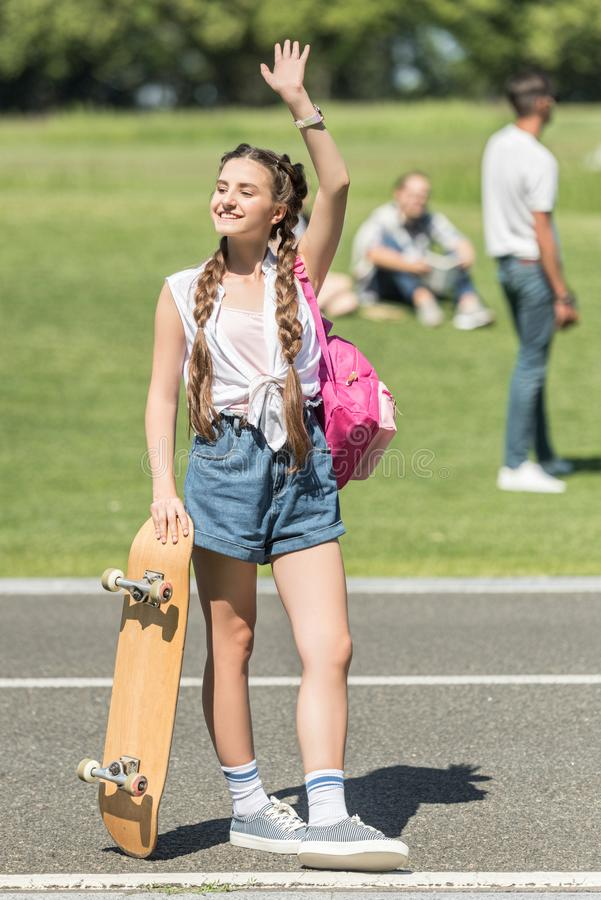 smiling teenage girl with skateboard and backpack waving hand and looking away stock images