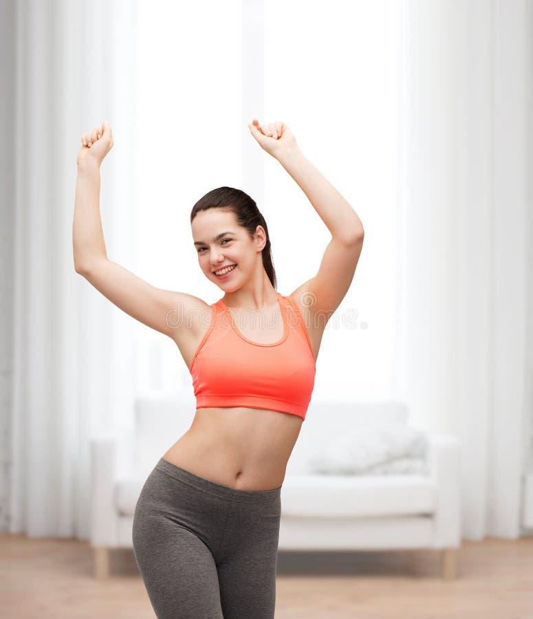 Smiling teenage girl in sportswear dancing. Fitness and diet concept - smiling teenage girl in sportswear dancing stock photography
