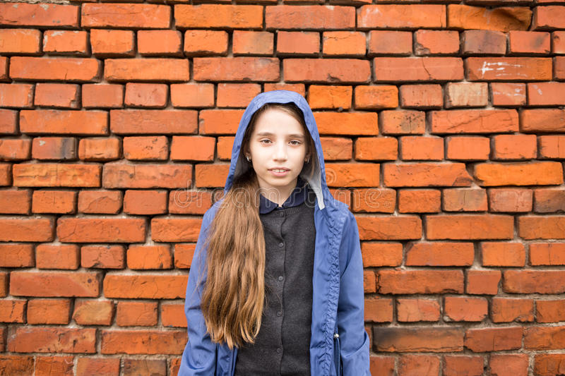 Smiling teenage girl standing against brick wall royalty free stock image