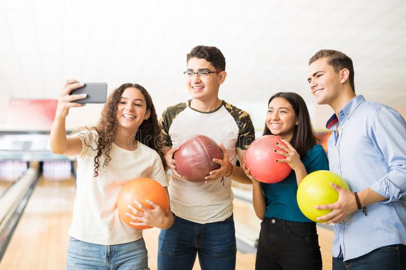 Teens Capturing Memories Of Bowling On Mobile Phone In Alley. Smiling teenage girls and boys capturing memories of bowling on mobile phone in alley at club royalty free stock photos