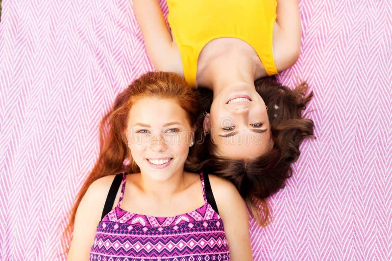 Smiling teenage girls lying on picnic blanket stock photo