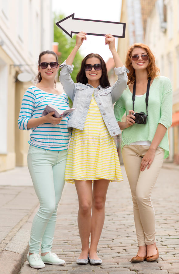 Smiling teenage girls with white arrow outdoors. Tourism, travel, vacation, direction and friendship concept - smiling teenage girls with white arrow showing royalty free stock photo
