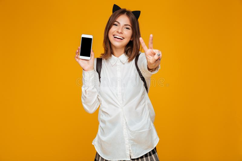 Smiling teenage schoolgirl in uniform with backpack. Holding blank screen mobile phone and showing peace gesture isolated over orange background royalty free stock photo