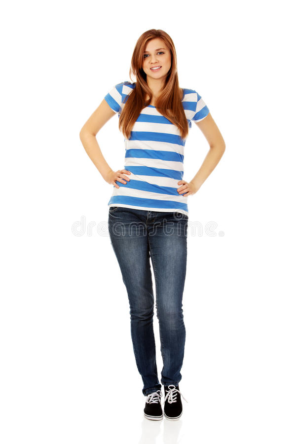Smiling teenage woman with hands on hips stock photo