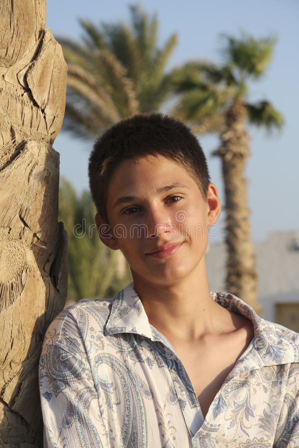 Smiling teenager boy near a palm royalty free stock photo