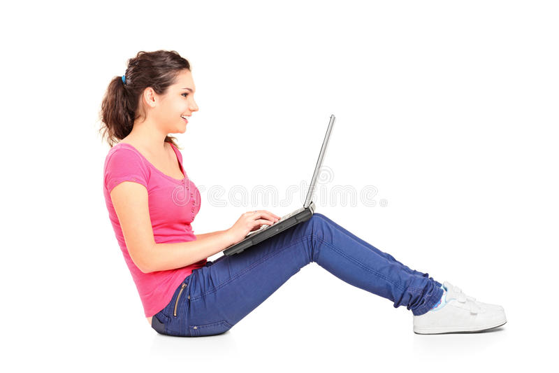 A smiling teenager doing her homework on a laptop