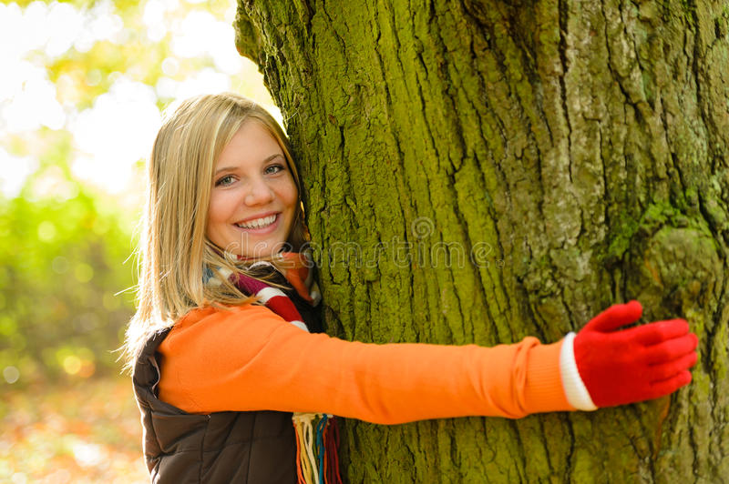 Smiling Teenager Girl Embracing Tree Autumn Woods Royalty Free Stock Photography