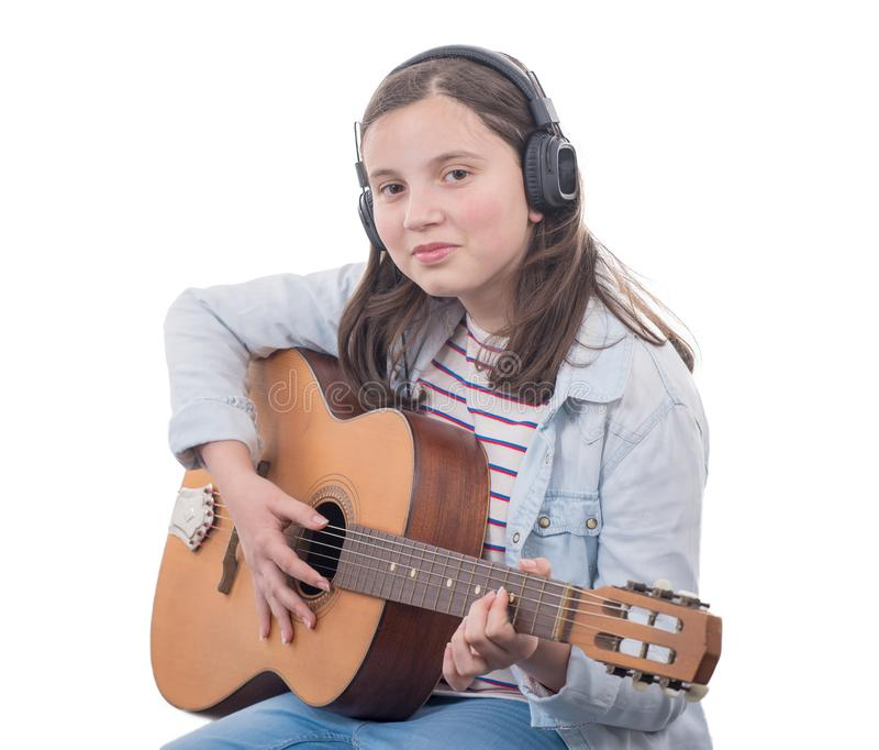 Smiling teenager girl playing acoustic guitar on white stock photography