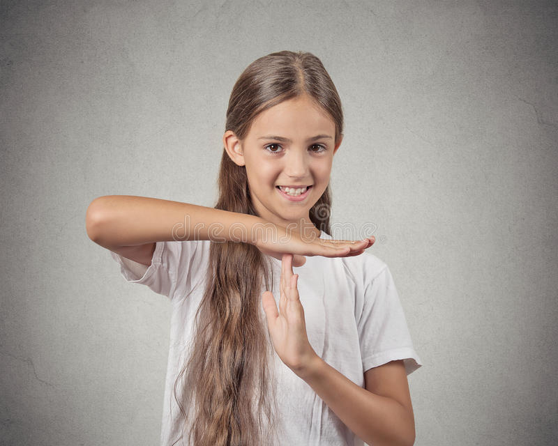 Smiling teenager girl showing time out gesture. Closeup portrait happy smiling teenager girl showing time out gesture with hands isolated grey wall background royalty free stock photo