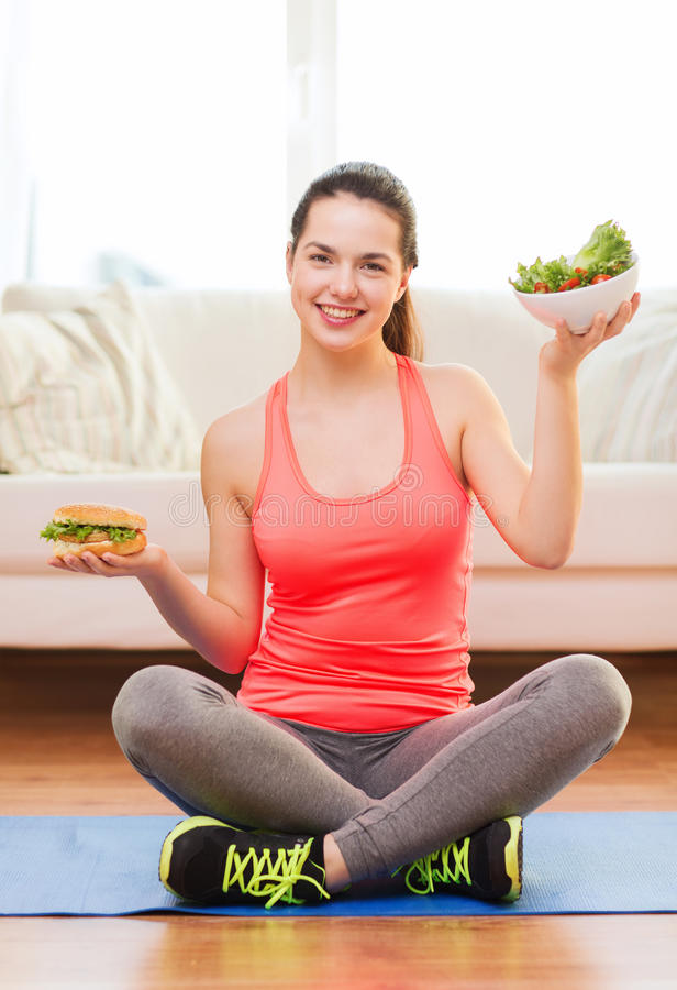 Smiling teenager with green salad and hamburger. Fitness, home and diet concept - smiling teenage girl with green salad and hamburger at home royalty free stock images