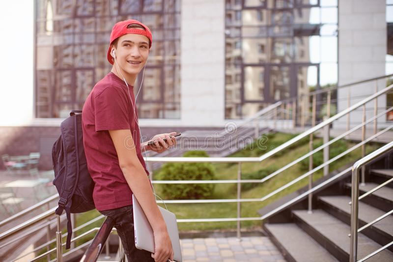 Smiling teenager holds cell phone and laptop, in the city.  Young man stands with a smartphone and computer, in the street. royalty free stock photo