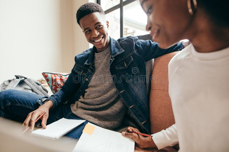 College students studying together in campus. Smiling teenager looking at girl reading book on sofa at university campus. College students studying together in stock images