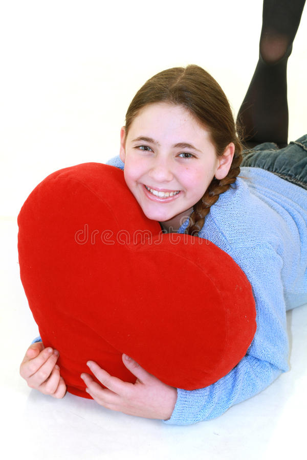 Smiling teenager with red haert. Beautiful smiling teenager with red heart isolated on white background stock photo