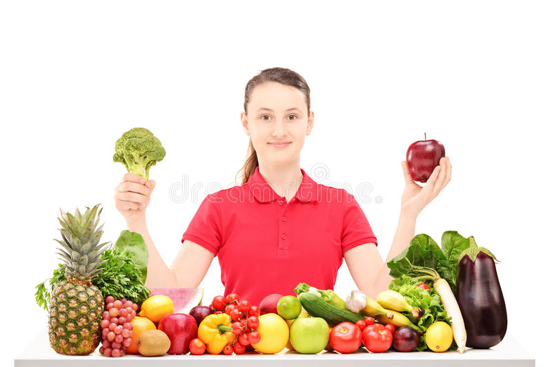 Smiling teenager sitting and holding apple and broccoli royalty free stock photo