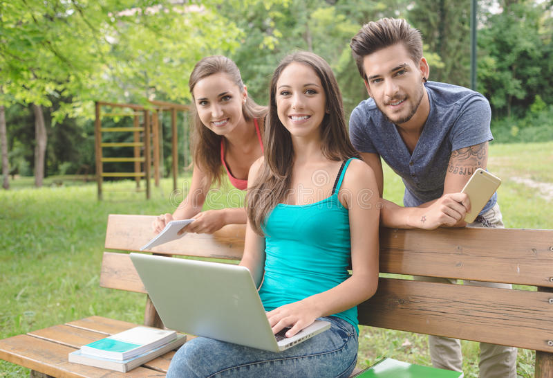 Smiling teenagers at the park using a computer. Cheerful young teenagers at the park, a girl is sitting on a bench using a computer, they are smiling at camera royalty free stock image