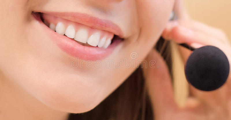 Smiling telemarketing operator. With microphone royalty free stock photography