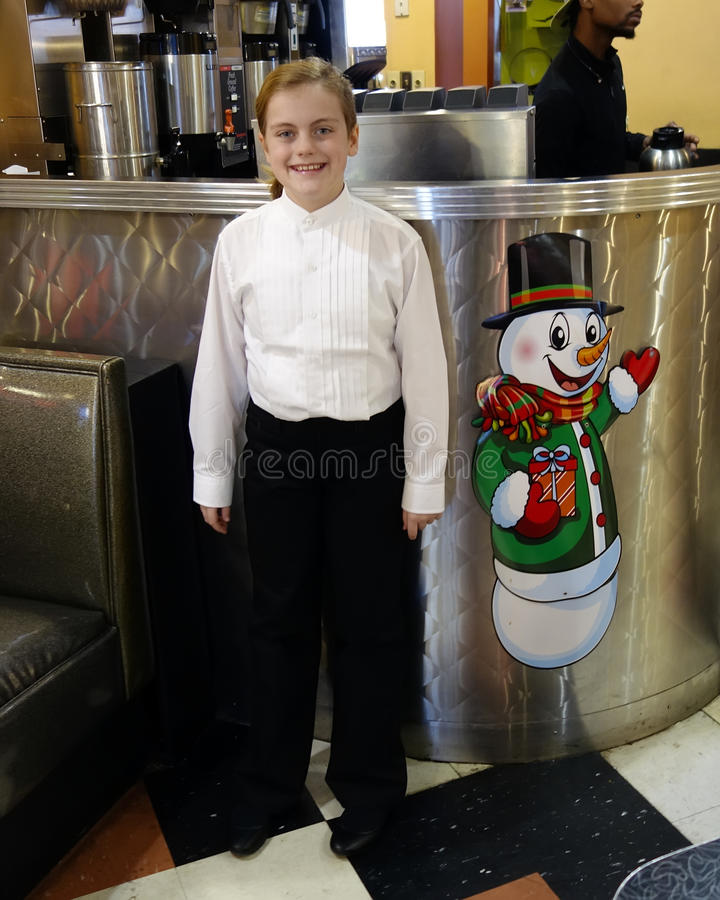 Smiling ten-year-old girl standing next to a picture of a snowman stock photography