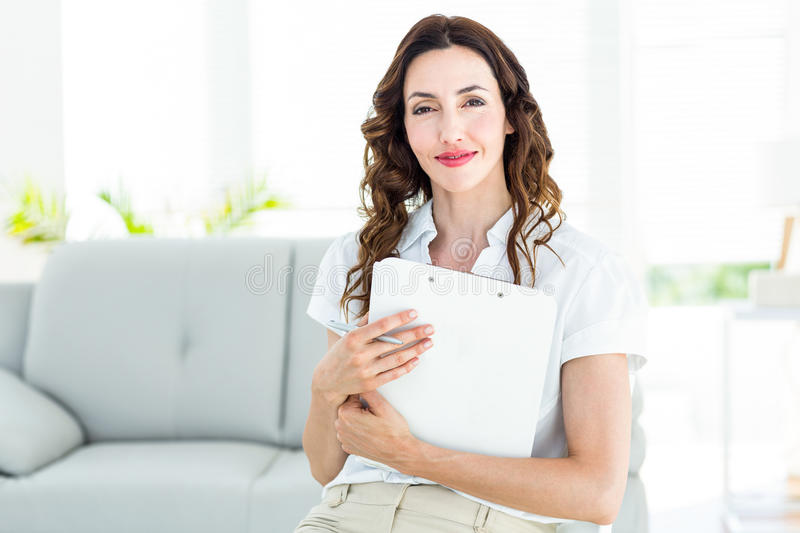 Smiling therapist holding her clipboard stock photo