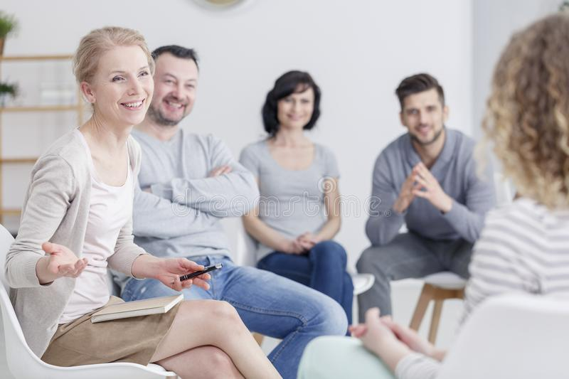 Smiling therapist talking to people stock photos
