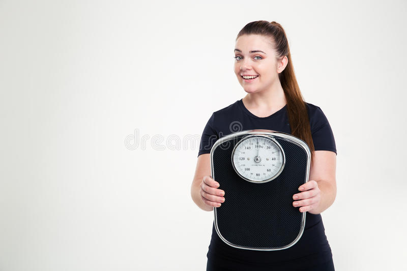 Smiling thick woman holding weighing machine. Portrait of a smiling thick woman holding weighing machine isolated on a white background royalty free stock photos