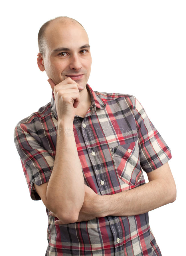 Smiling thinking young man with hand on chin stock photography