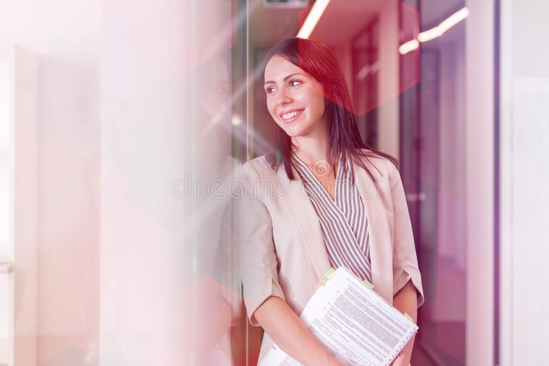 Smiling thoughtful businesswoman with documents at office royalty free stock image