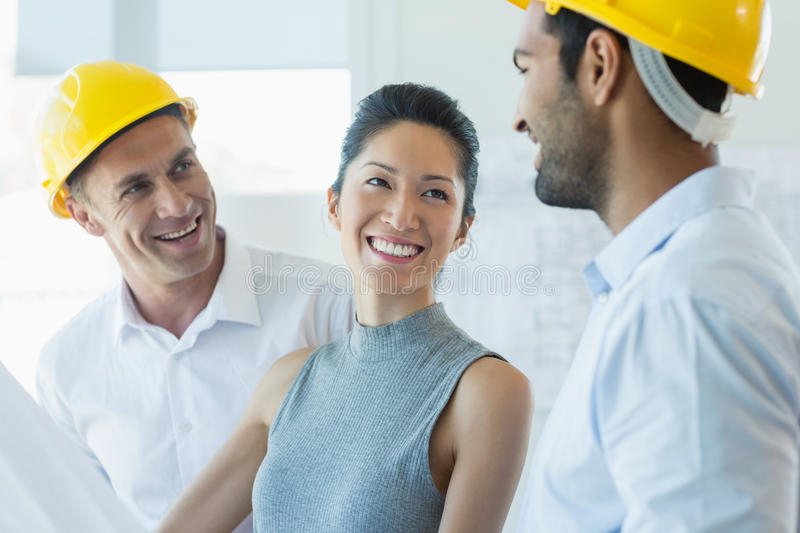 Smiling three architects interacting with each other royalty free stock image