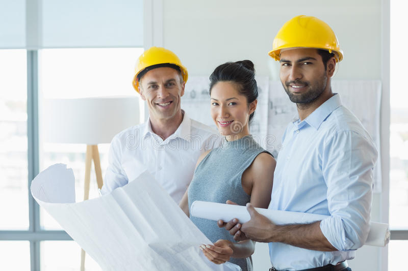 Smiling three architects standing in office with blueprint stock photos