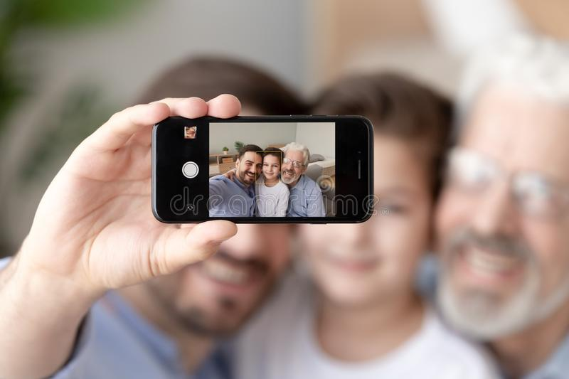 Smiling three generations of men take selfie on smartphone. Smiling dad, little son and grandfather sit on couch make self-portrait picture on smartphone, happy stock photos