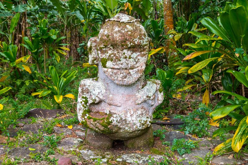 Smiling tiki. Carved stone Polynesian sacred idol statue. Raivavae island, Astral islands, French Polynesia, Oceania. royalty free stock photography