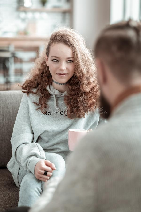 Curly teenage girl smiling to her private counselor while talking. Smiling to counselor. Curly dark-haired teenage girl smiling to her private counselor while stock photo