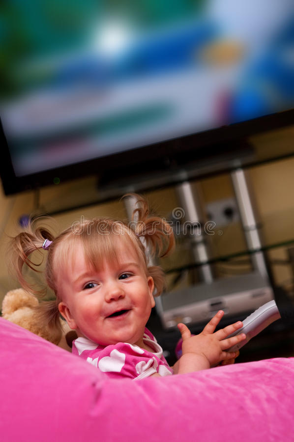 Smiling toddler. Holding television remote control royalty free stock image