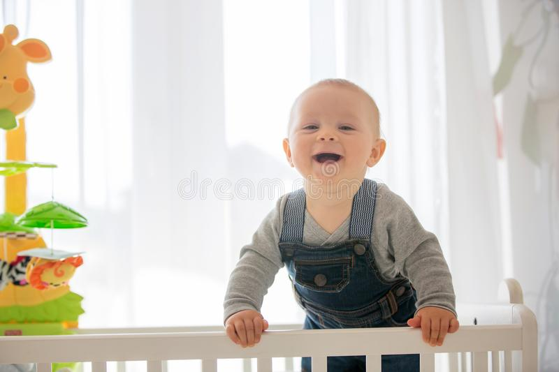 Smiling toddler boy, playing with little rabbit toy in crib. Smiling happily stock image