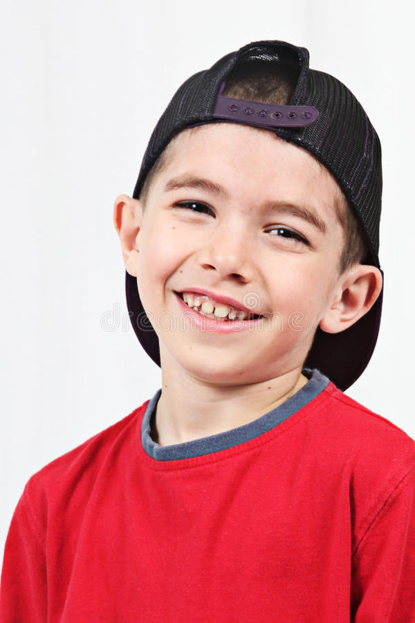 Smiling toddler in cap. Portrait of smiling male toddler with baseball cap wrong way around, white studio background stock image