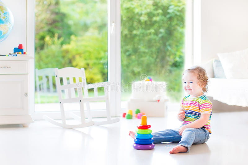 Smiling toddler girl playing with a pyramid toy. In a white room royalty free stock images