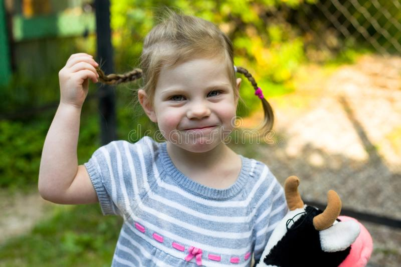 Smiling toddler little blond girl with plaits close up photo royalty free stock images