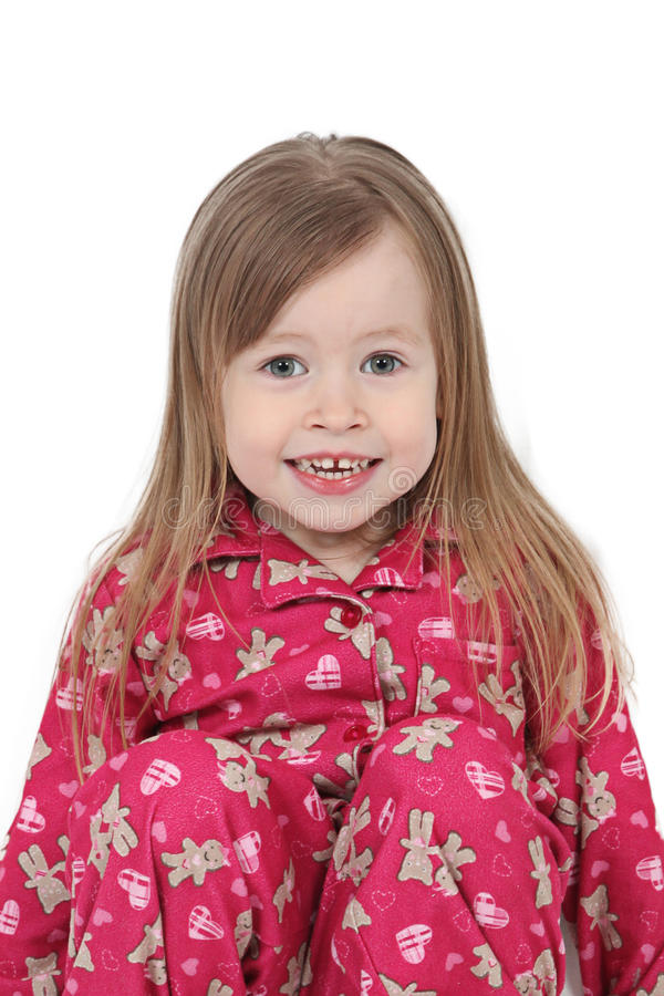 Smiling toddler in pajamas. Portrait of smiling preschool girl or toddler in red pajamas or pyjamas, isolated on white background royalty free stock photo