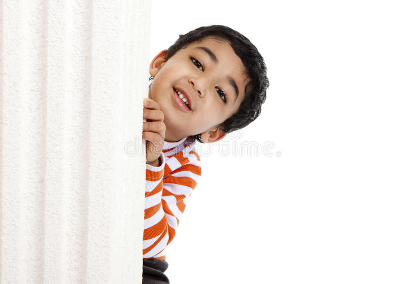 Smiling Toddler Peeks from Behind a Column. Isolated, White royalty free stock photos