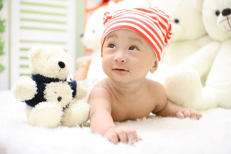 Smiling Toddler Wearing Orange And White Knit Cap Beside Black And White Bear Plush Toy Free Public Domain Cc0 Image