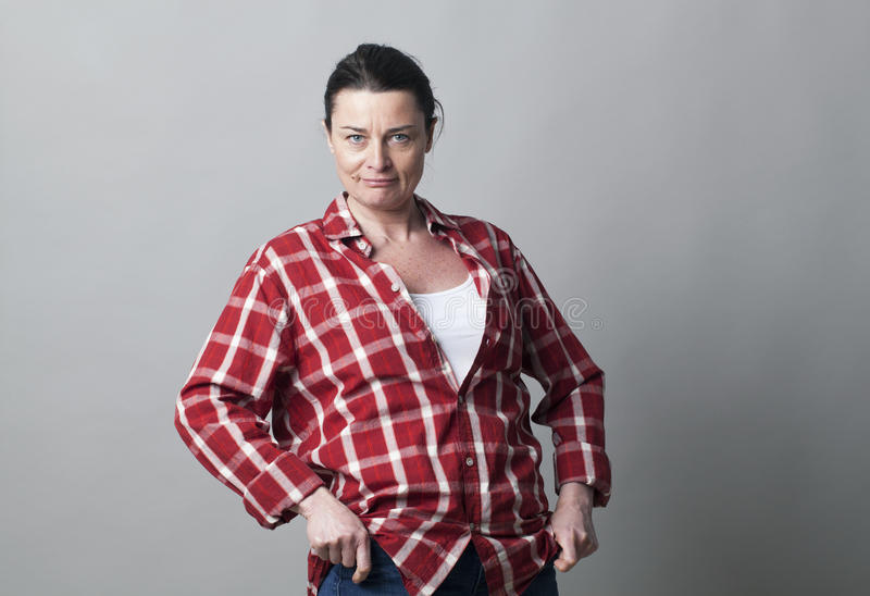 Smiling tomboy mature woman standing showing her wellbeing. Smiling tomboy mature woman standing with hands on hips showing her wellbeing and gender attitude stock images